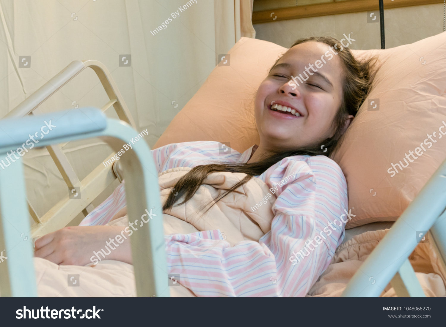 Laughing mixed race Asian American tween girl in hospital bed
