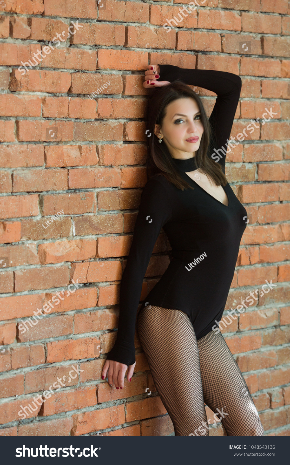 beautiful young slender girl in black bodie standing near a brick wall #1048543136