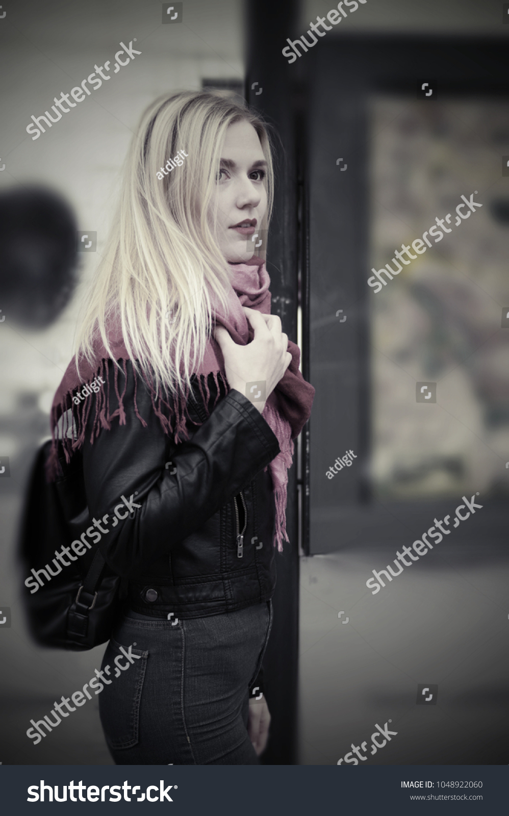 A beautiful blonde girl is standing at a public transport stop. The girl