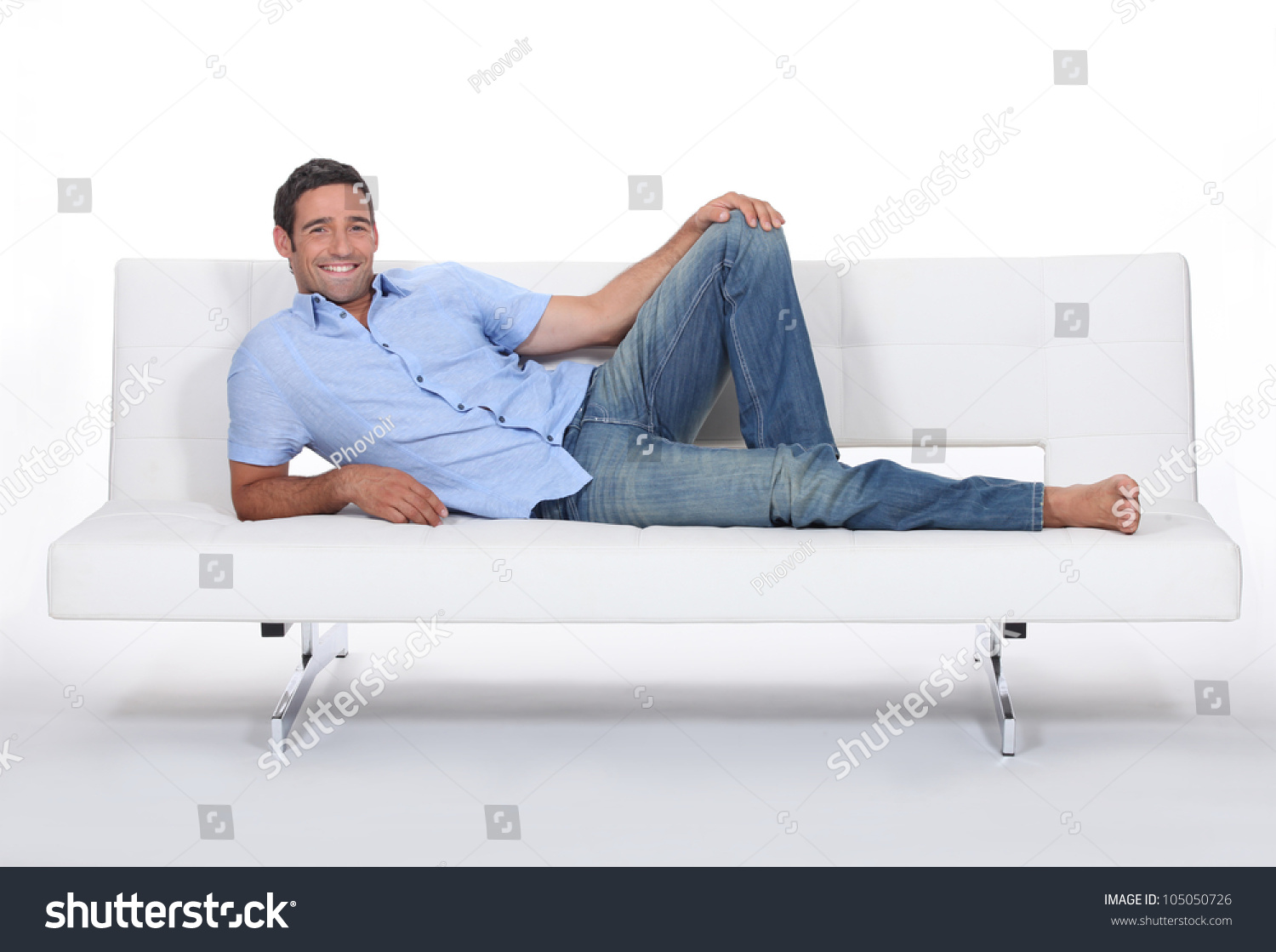 Royalty-free Barefoot man lying on a couch #105050726 Stock Photo ...