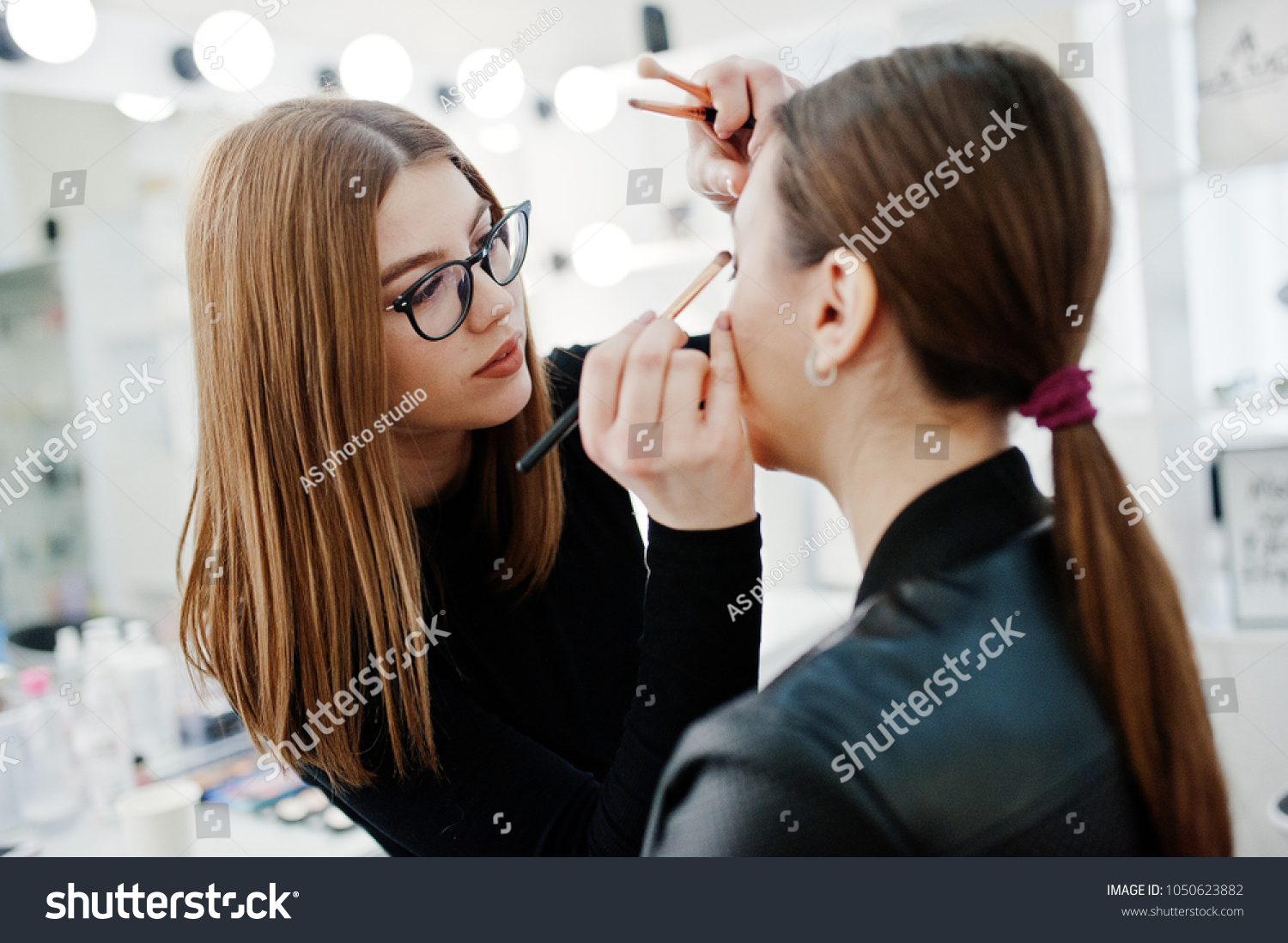 Make up artist work in her beauty visage studio salon. Woman applying by professional make up master. Beauty club concept. #1050623882