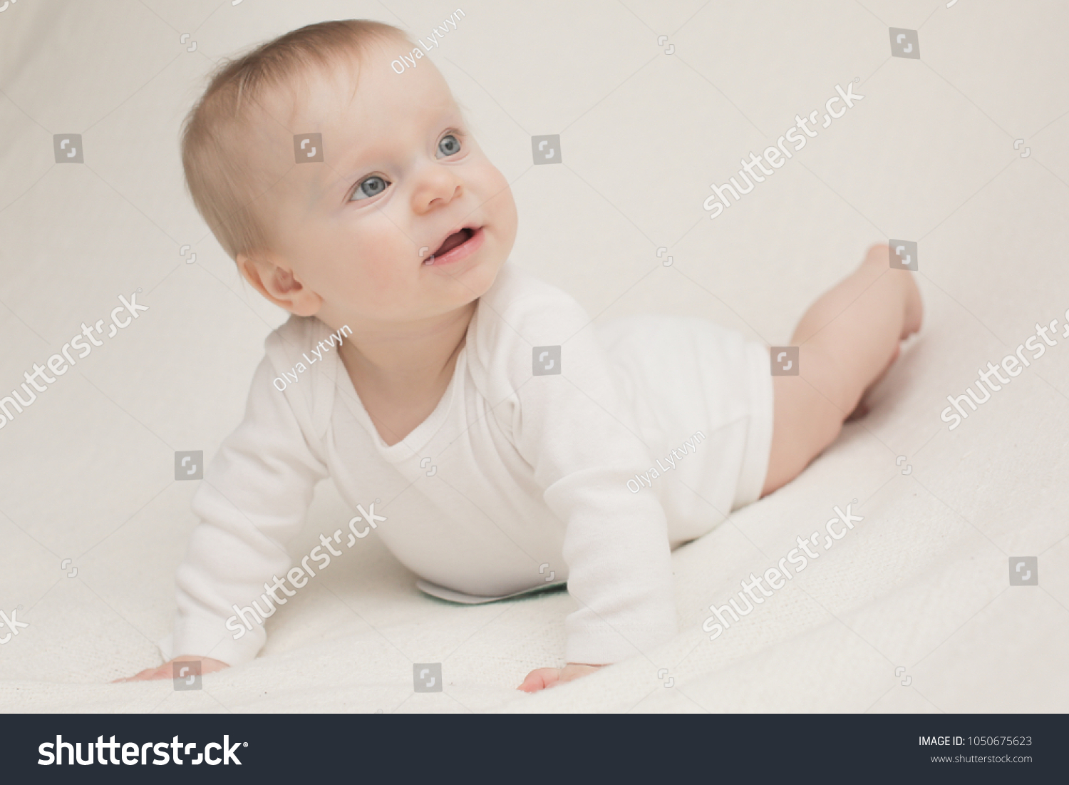 A 8 month old happy baby girl in front of a white background blonde
