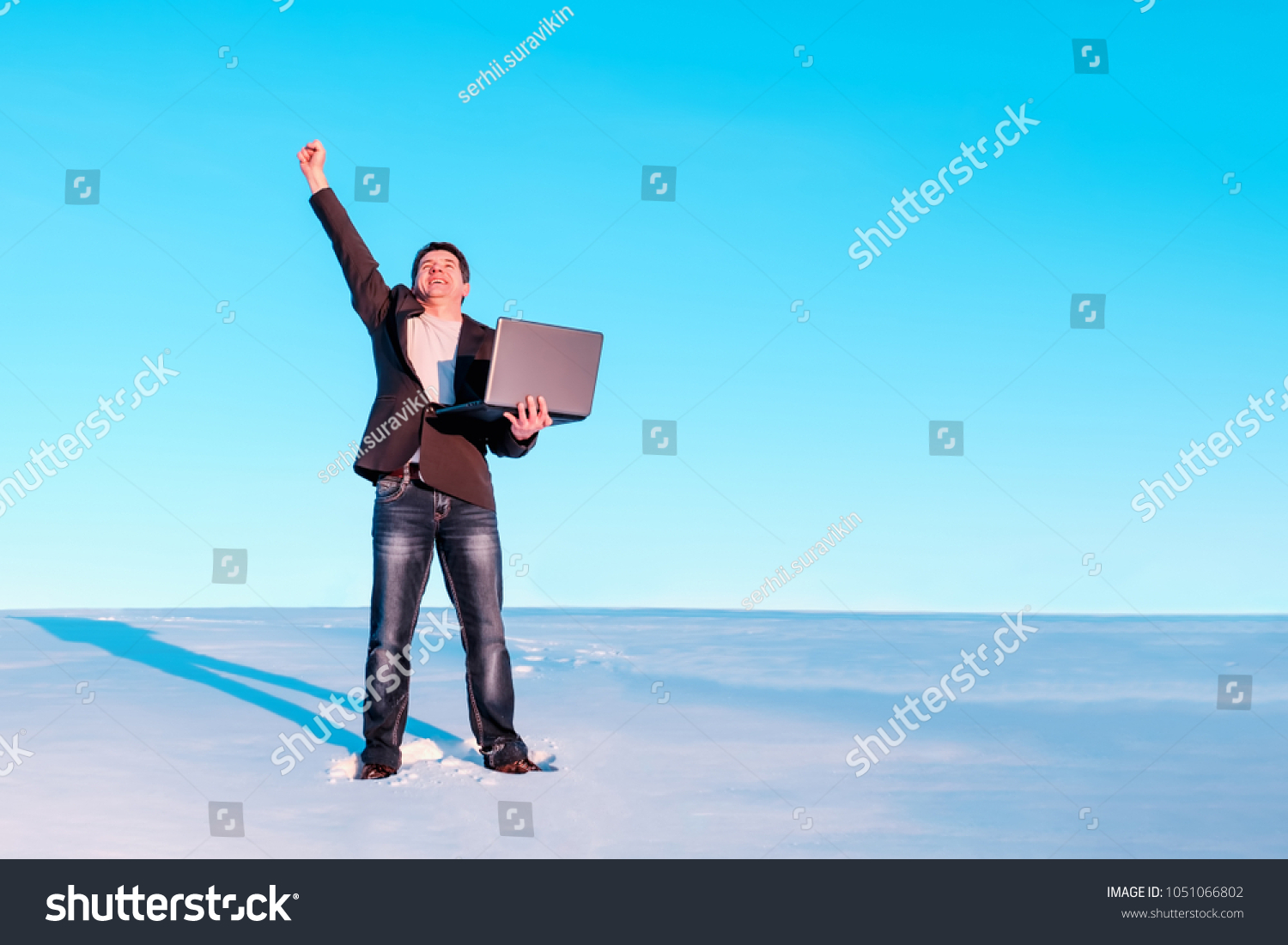 Freelancer with a laptop joyfully raised his hand. The concept of success and work in any setting. #1051066802