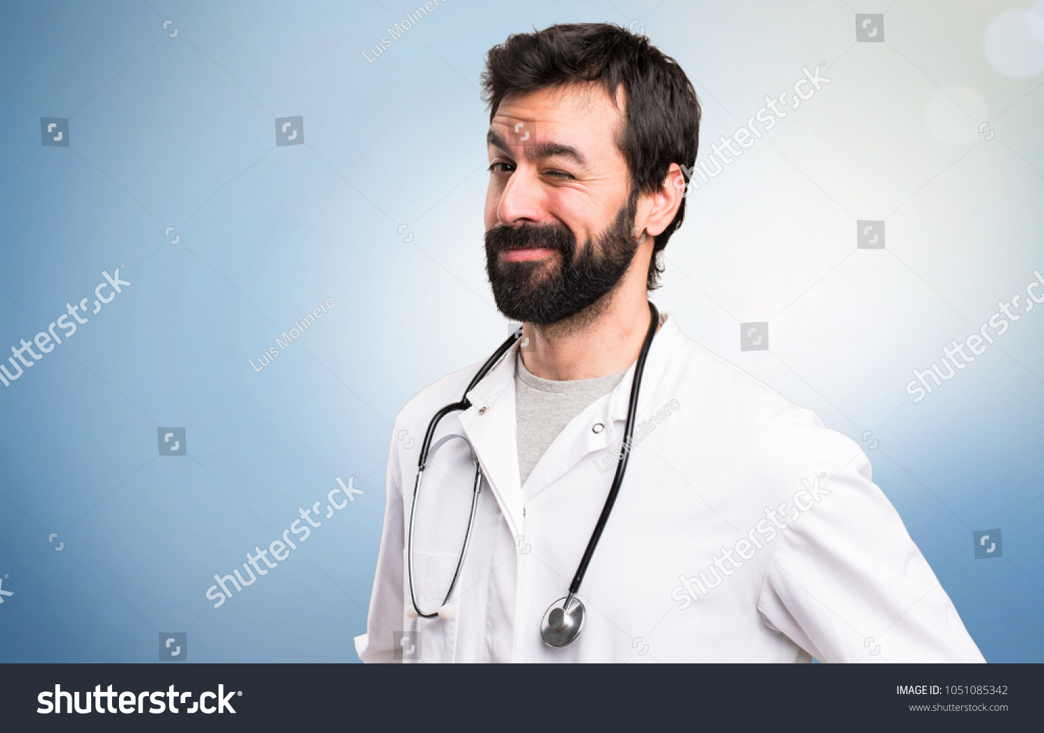 stock-photo-young-doctor-winking-on-blue