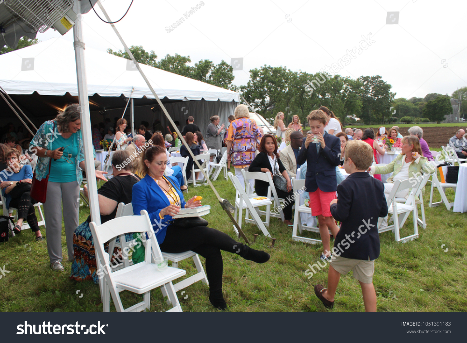 Book Fair Reception East Hampton, NY USA August 12 2017 People sitting at tables and underneath tents eating and drinking and walking in the field