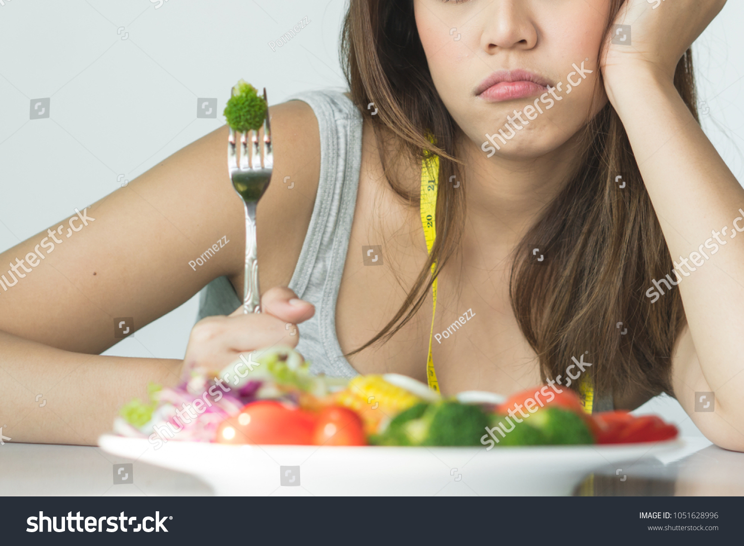 unhappy asian women is on dieting time looking at broccoli on the fork. girl do not want to eat vegetables and dislike taste of broccoli. #1051628996