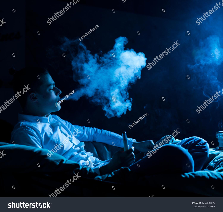 Young handsome guy smoking hookah alone closeup blur studio black background blue filter