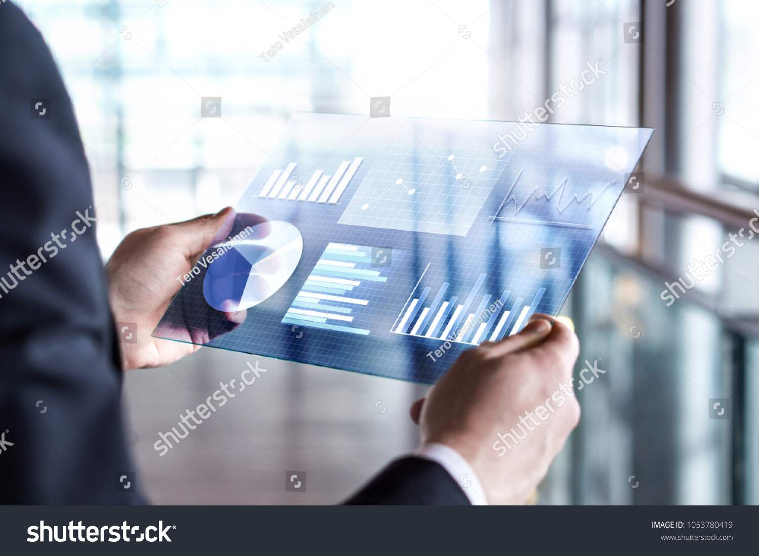 Transparent futuristic tablet. Business man using virtual touch screen. Modern mobile technology in accounting, finance, data and analytics. Internet of things (IOT) and augmented reality concept. #1053780419