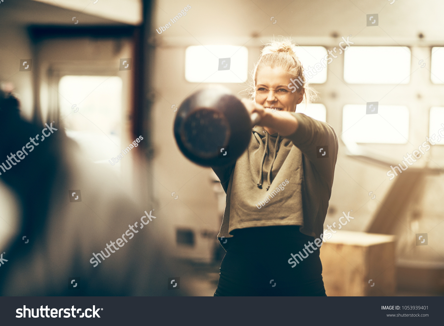Smiling young woman in sportswear swinging a dumbbell during an exercise  session in a gym