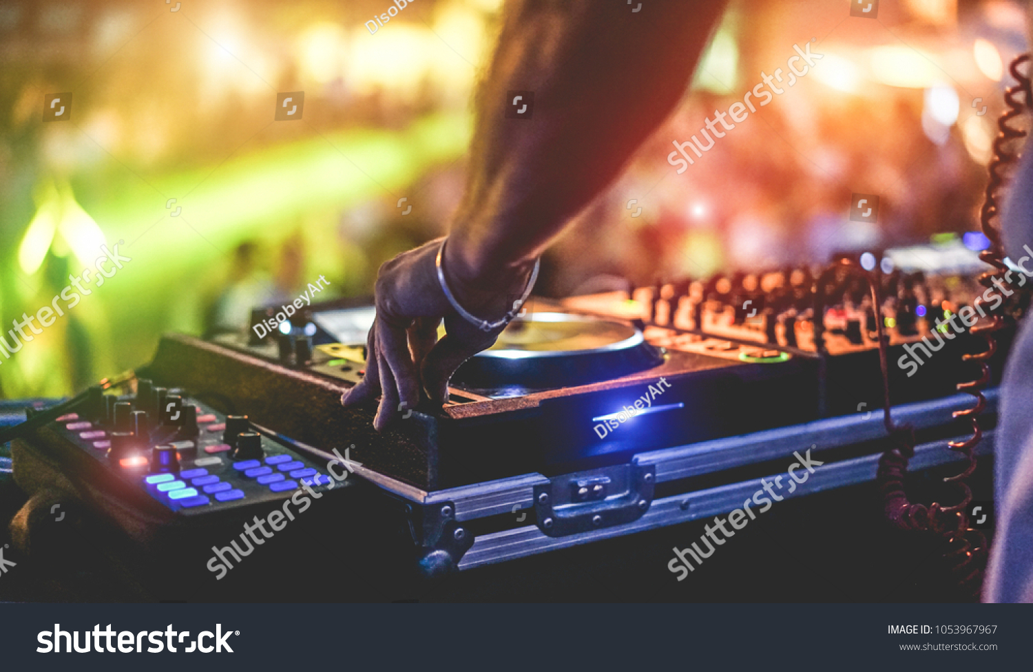 Dj mixing outdoor at beach party festival with crowd of people in background - Summer nightlife view of disco club outside - Soft focus on hand fingers - Fun ,youth,entertainment and fest concept #1053967967