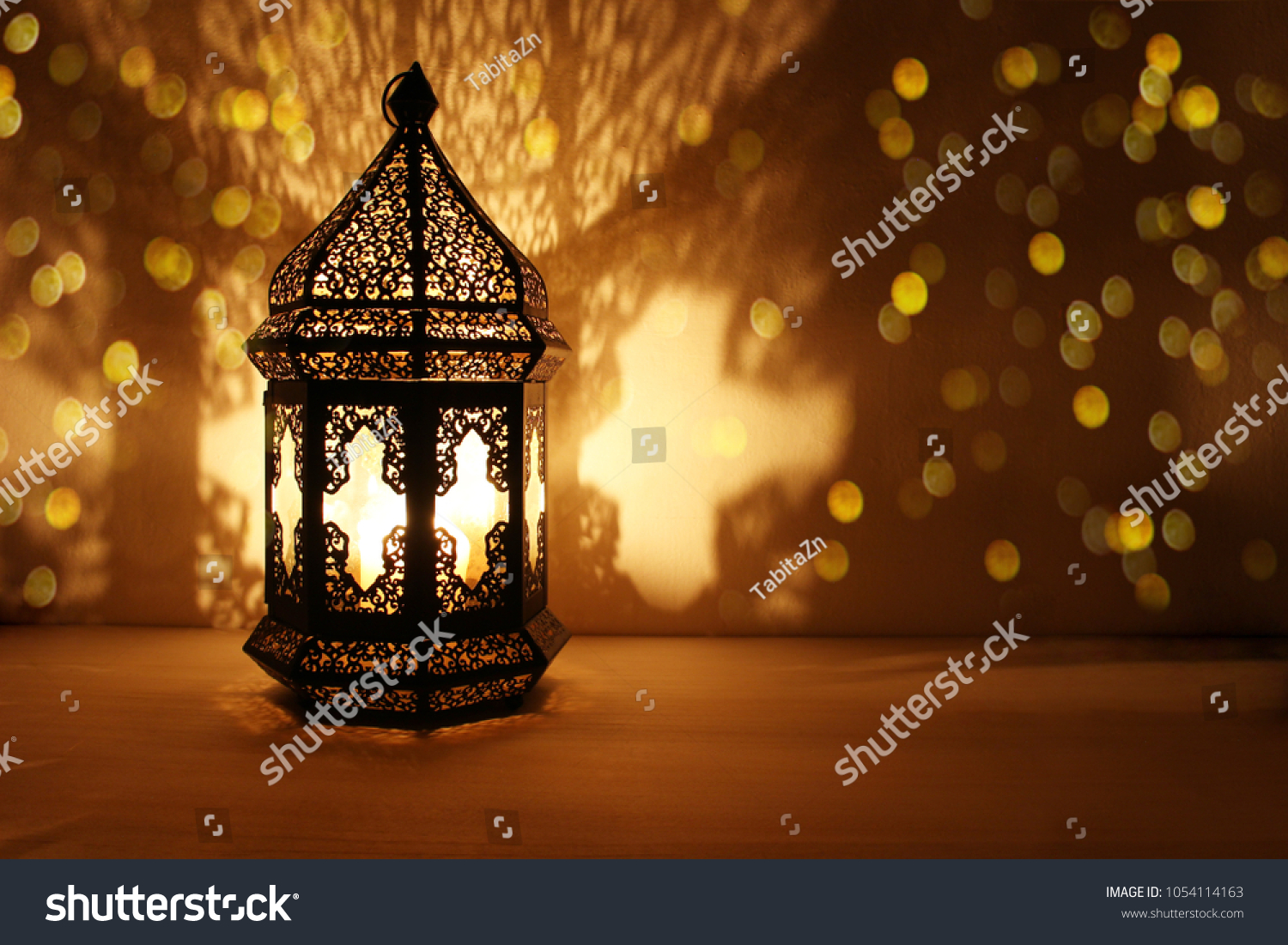 Ornamental Arabic lantern with burning candle glowing at night and glittering golden bokeh lights. Festive greeting card, invitation for Muslim holy month Ramadan Kareem. Dark background. #1054114163