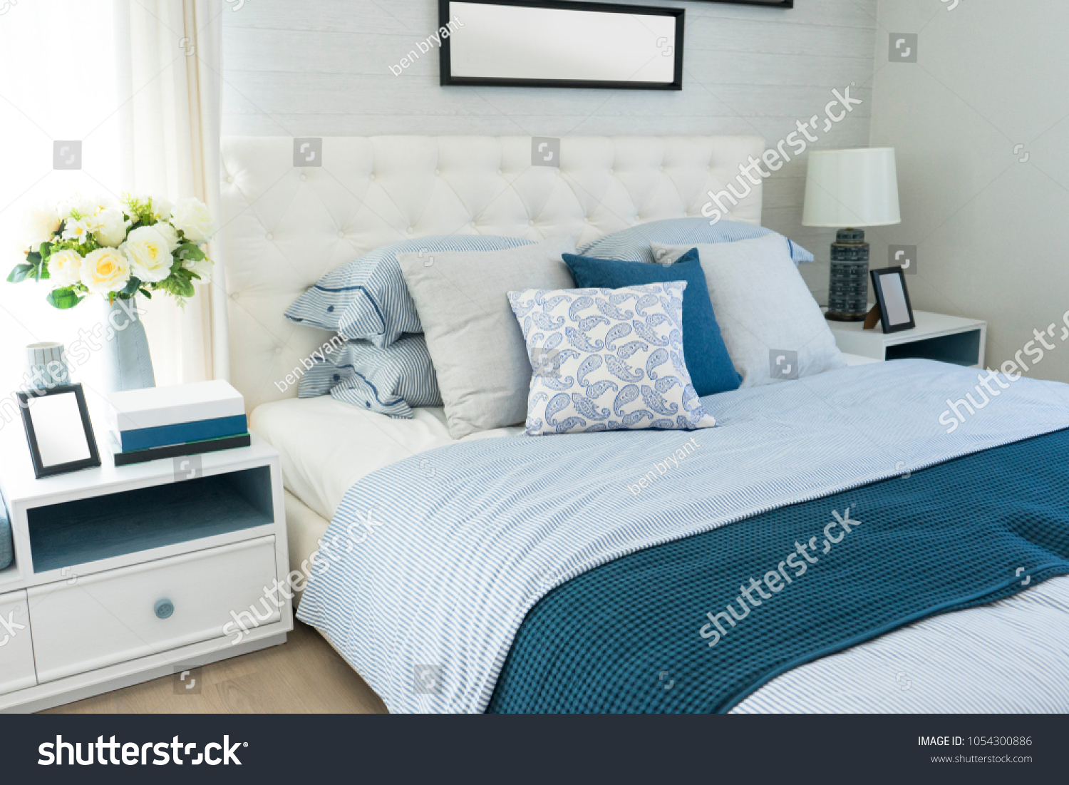 Blue bedroom interior with navy blue pillows against white wall with gallery of posters