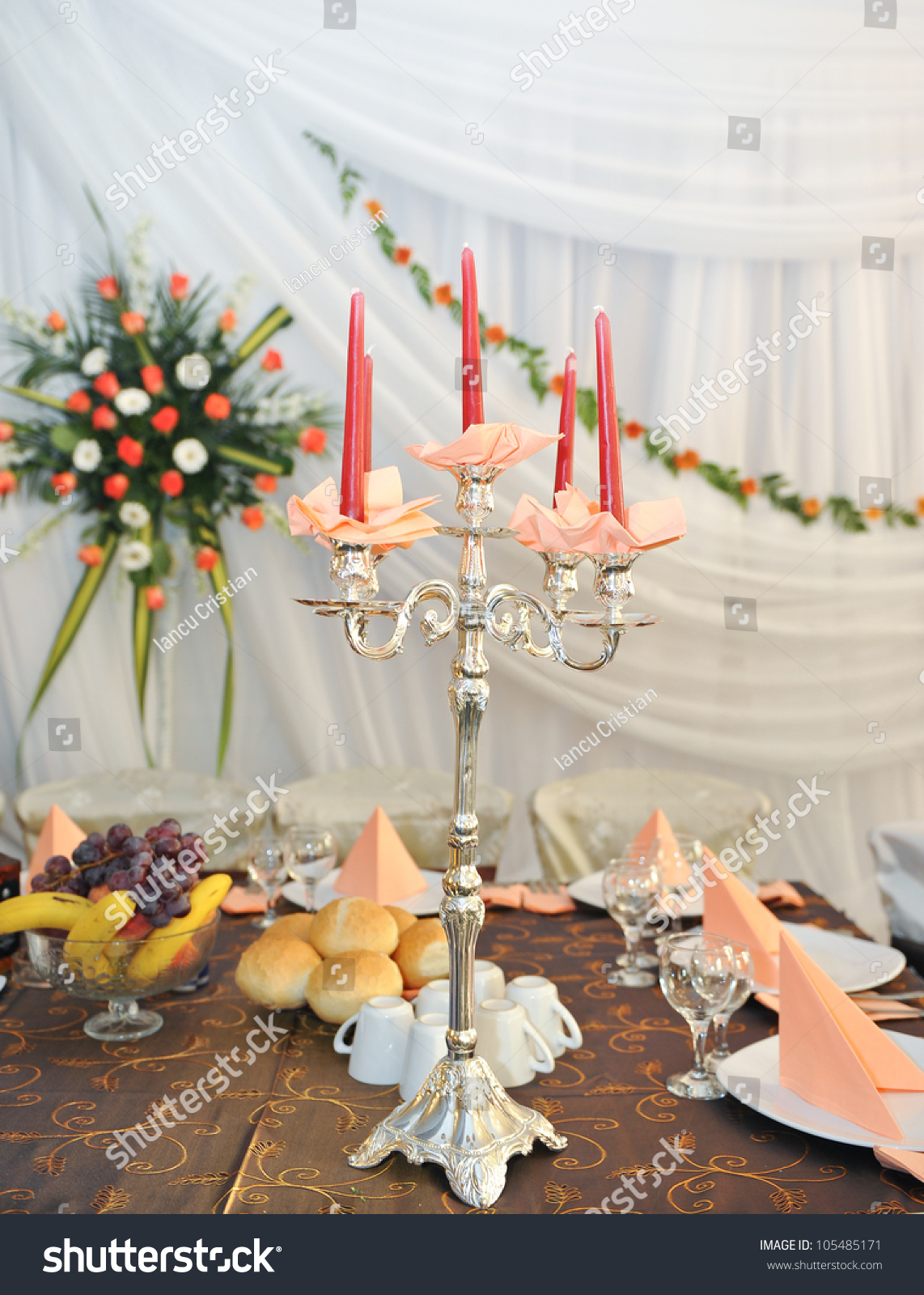 Candlestick With Candles And Floral Arrangements On Wedding Ceremony Detail