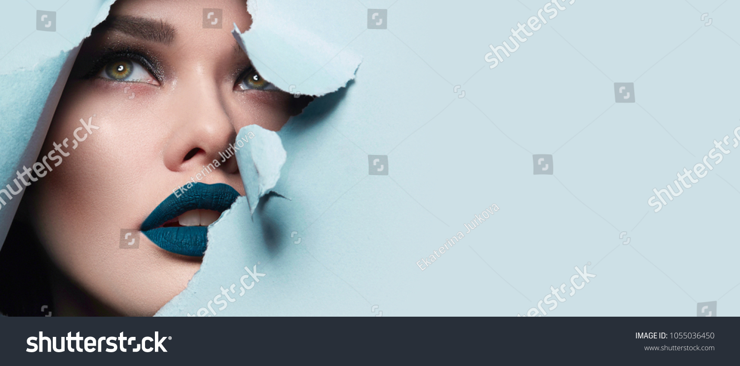 the face of a young beautiful girl with a bright make-up and puffy blue lips peers into a hole in blue paper.Fashion, beauty, make-up, cosmetics, hairstyle, beauty salon, boutique, discounts, sales. #1055036450