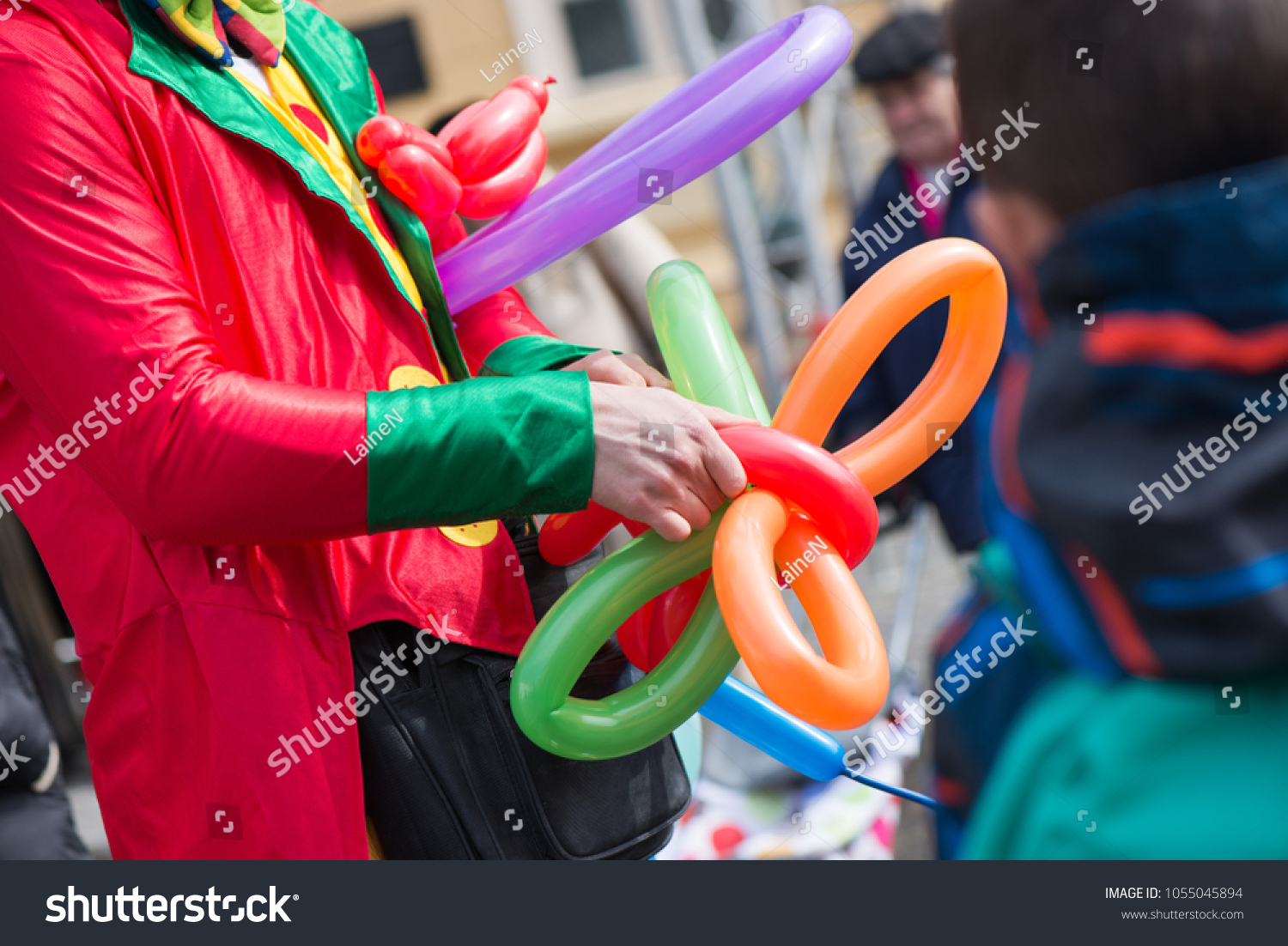 A freelance clown creating balloon animals and different shapes at outdoor festival in city centre. School bag, angel wings, butterflies and dogs made of balloons. Concept of entertainment, birthdays #1055045894