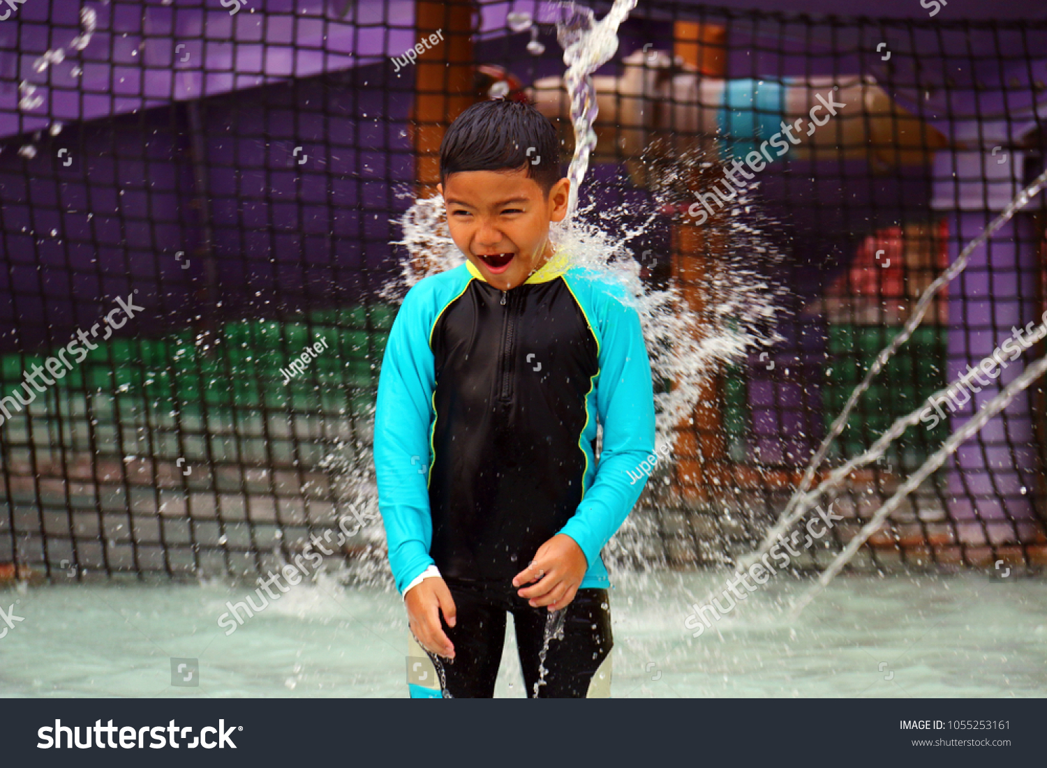 9d457bf18b A boy wearing a swimsuit standing and have water   falling into a water  splash