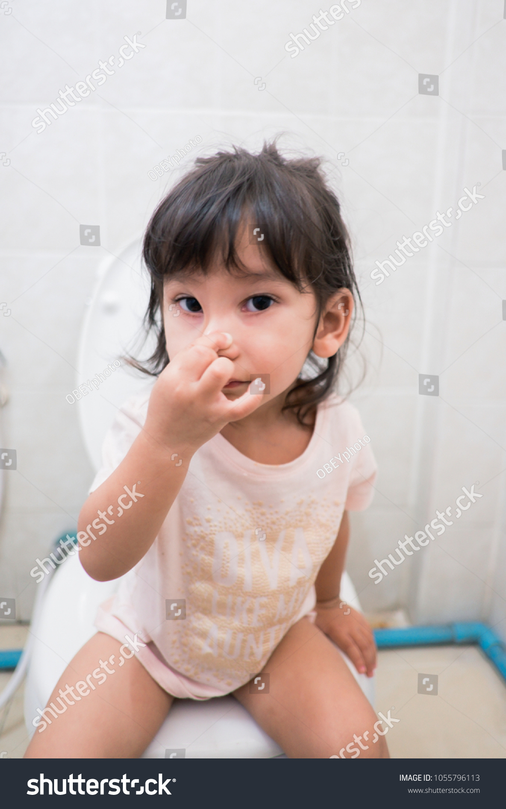 Little asian girl sitting on a toilet,Training child concept.Little girl  poo and pee in white toilet. - Image