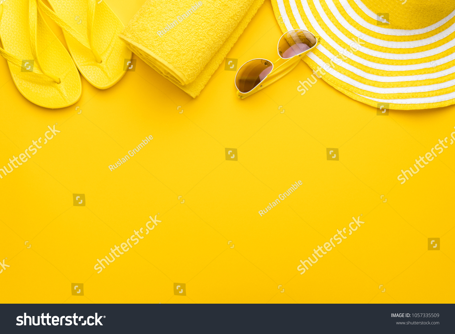 beach accessories on the yellow background - sunglasses, towel. flip-flops and striped hat. summer is coming concept #1057335509 - 123PhotoFree.com