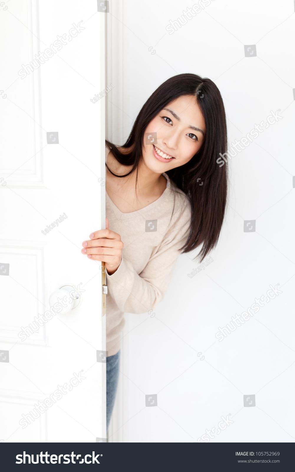 attractive asian woman opening door