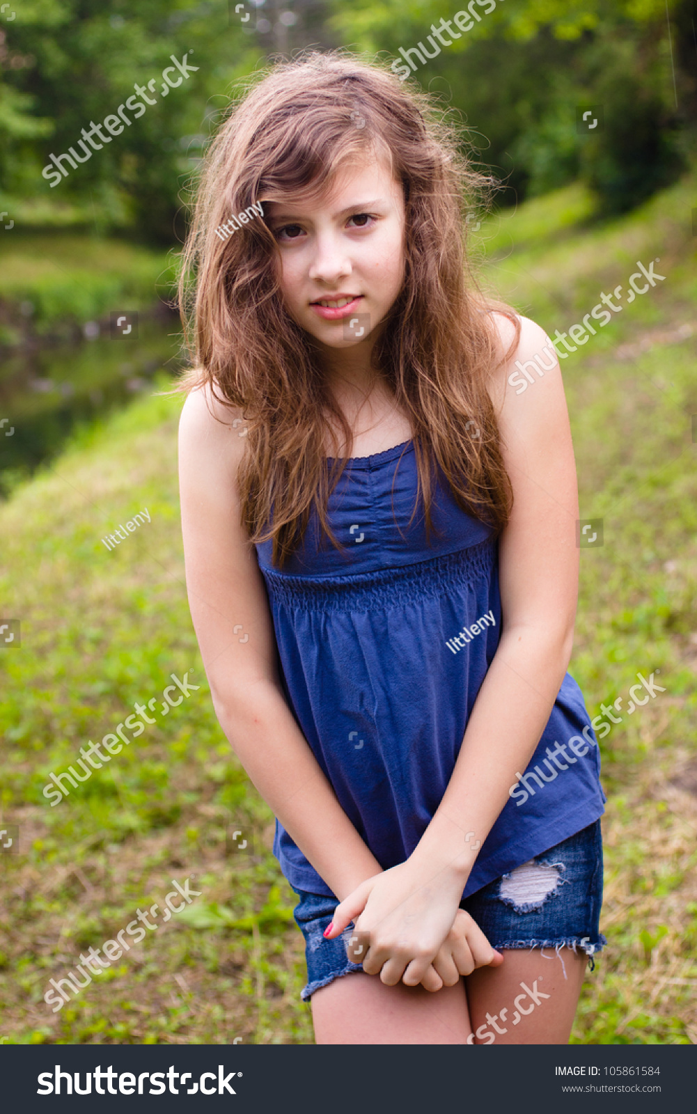 cute teenage girl looking shy in natural outdoor setting. Black Bedroom Furniture Sets. Home Design Ideas