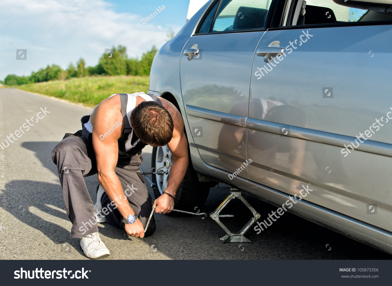 Design of car jack - Mechanic Lifting A Car With Jack Screw