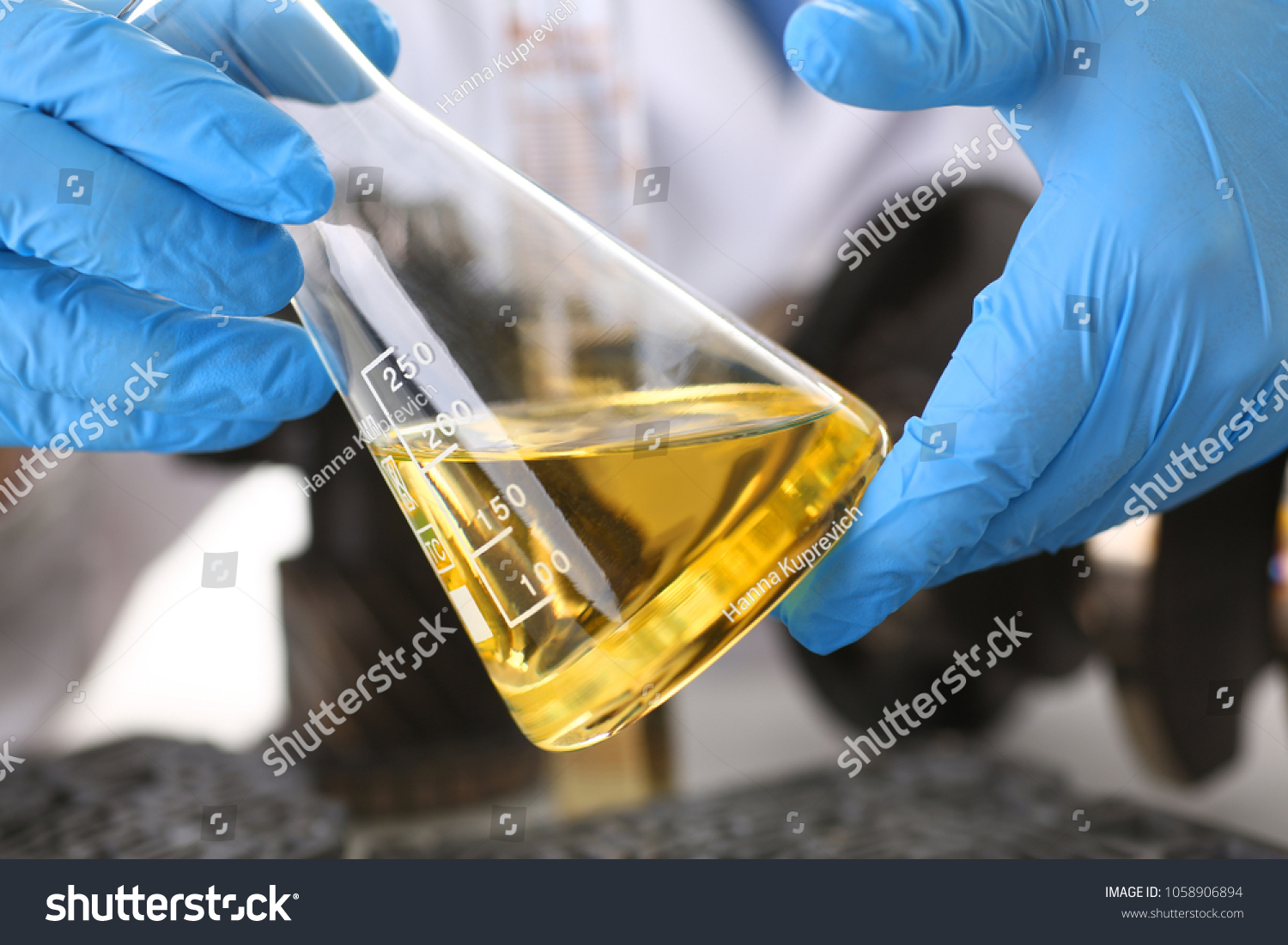 Male hands in protective gloves hold test tube in hands produces chemistry test of motor oil automatic gearbox and hydraulic booster #1058906894