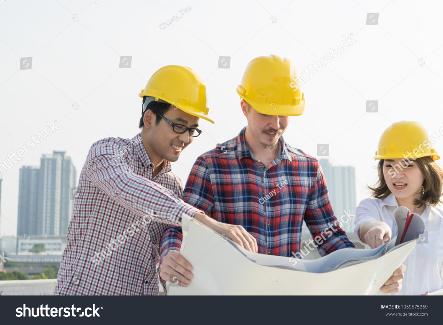 Multiethnic group young civil engineers worker stock photo safe to multiethnic group of young civil engineers worker and architects discussing on drawingblueprint construction malvernweather Images