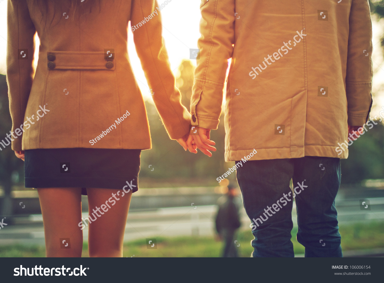 Happy Couple Holding Hands Looking In The Sunset Stock
