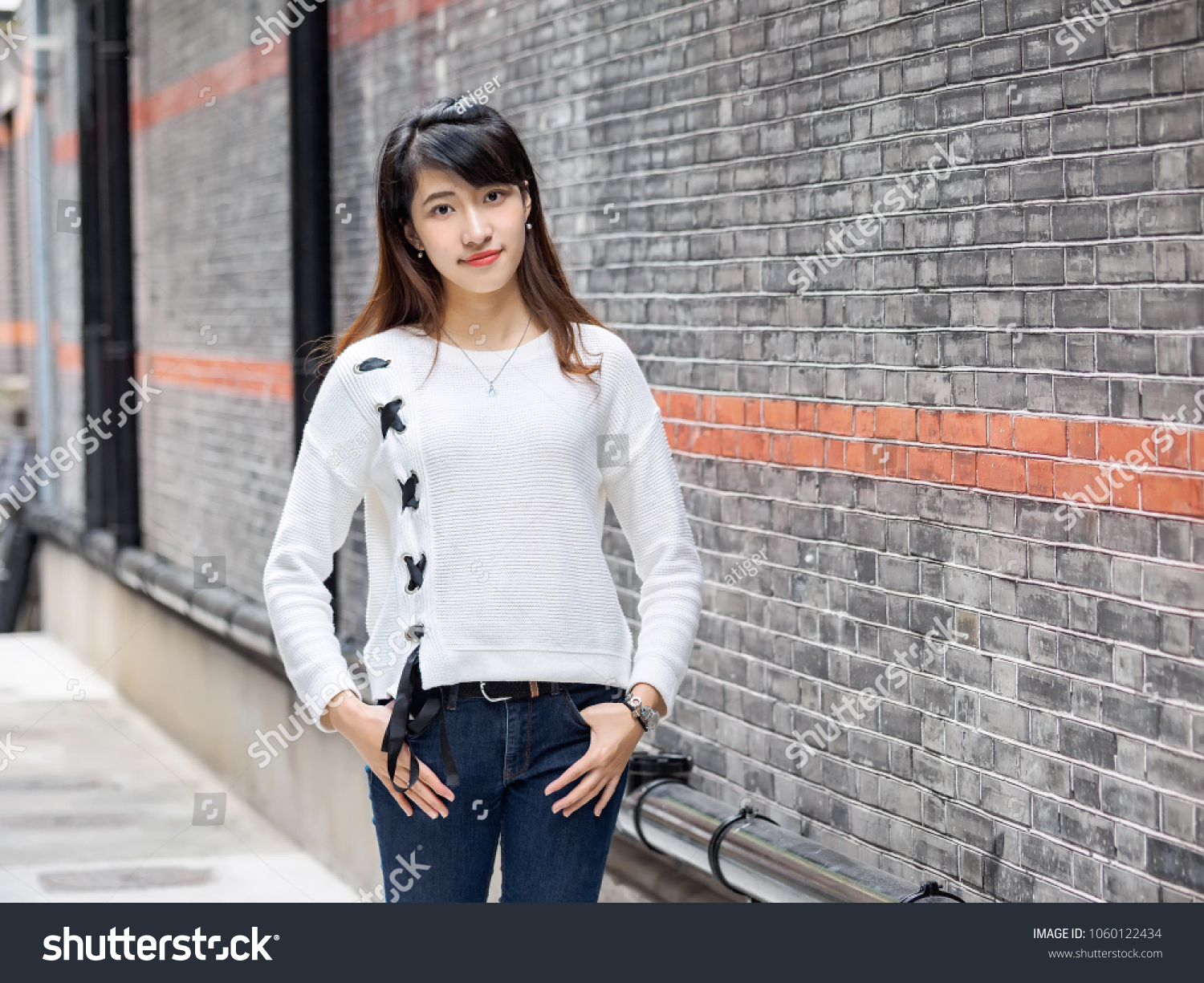 20c21fbd87e Portrait of beautiful young Chinese woman wearing white sweater and blue  jeans in Shanghai Xintiandi