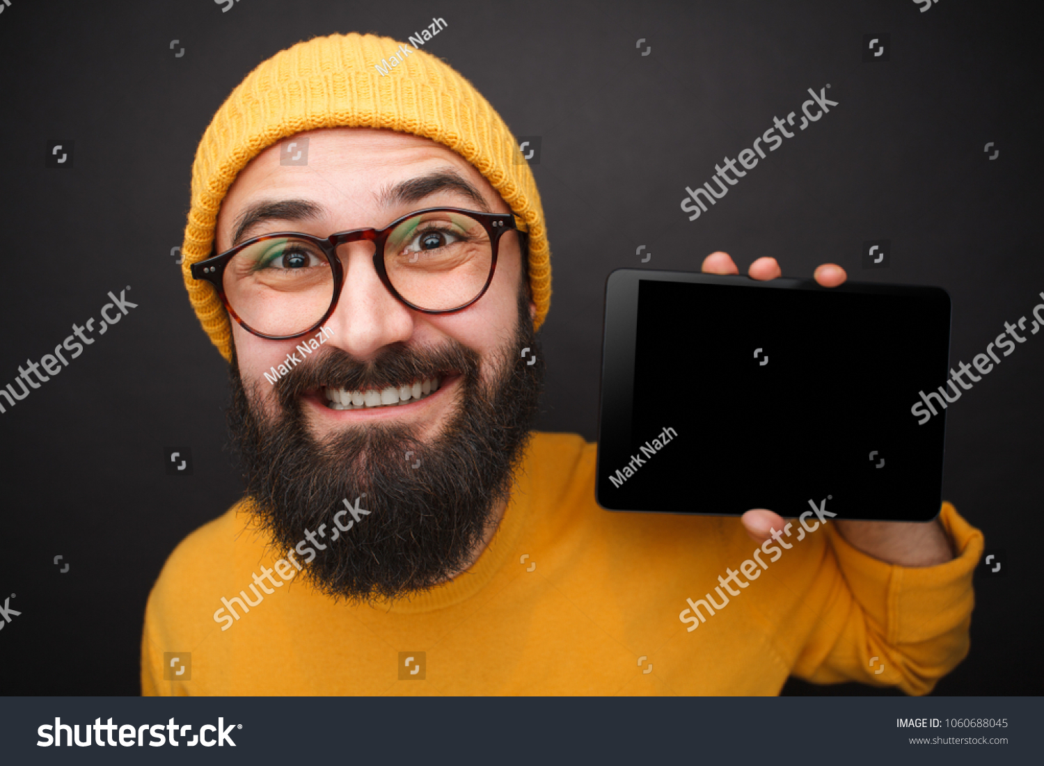 Handsome bearded man in hat and glasses promoting new contemporary tablet  on black background. 055634760c76