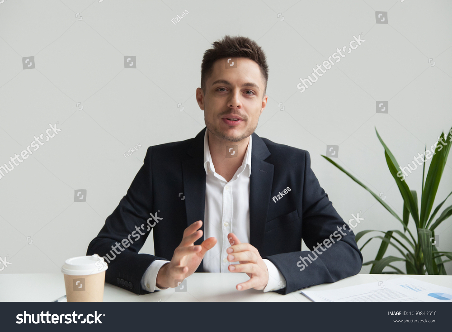 Confident CEO looking at camera talking about company strategy and business plan, explaining corporate success. Young entrepreneur shooting for online webinar, recording video blog. Headshot portrait #1060846556