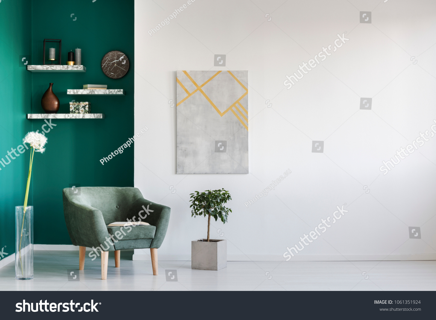 Green armchair between dandelion and plant in living room interior with copy space and grey painting #1061351924