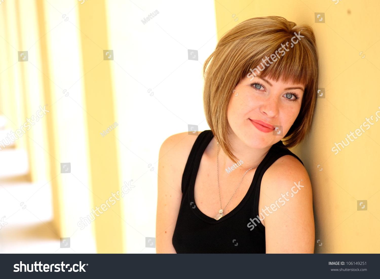 Stunning brunette beauty near yellow wall outdoors