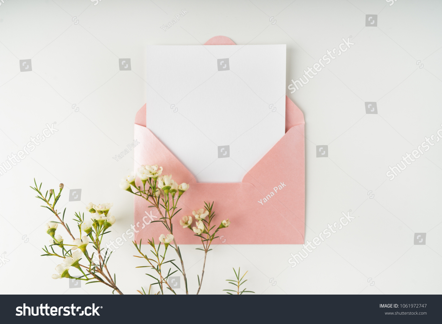 Minimal composition with a pink envelope, white blank card and a wax flower on a white background. Mockup with envelope and blank card. Flat lay. Top view. #1061972747