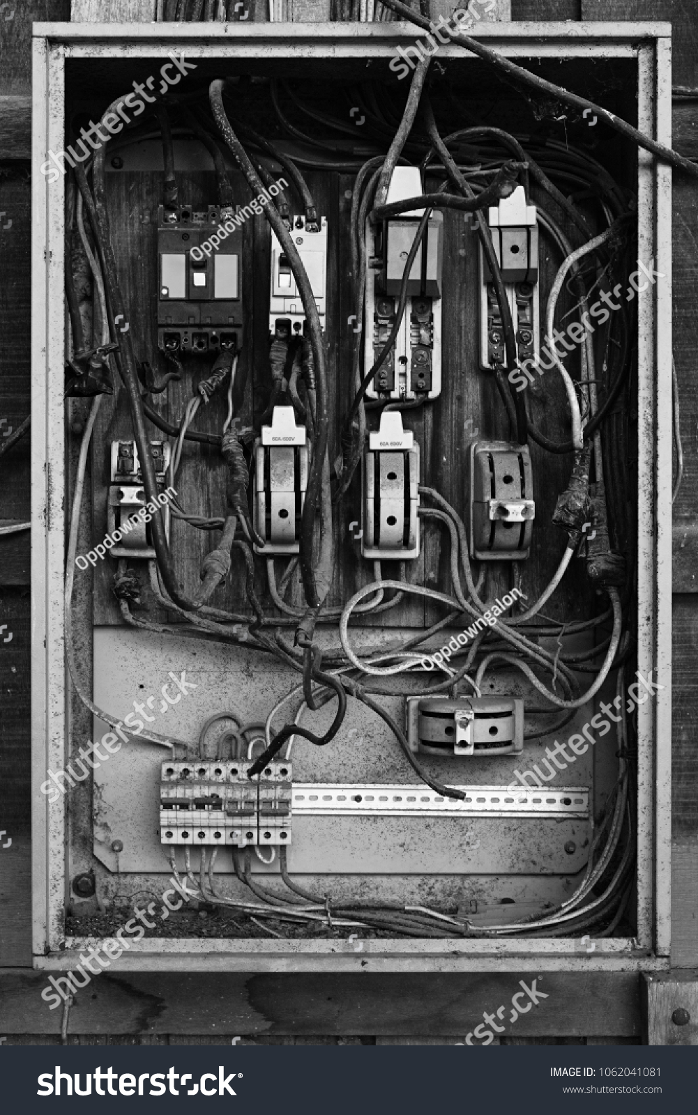 Old electric breaker box with wires and fuses in black and white