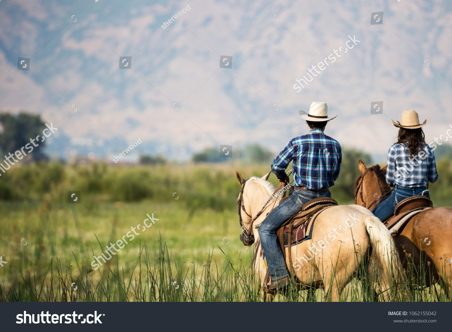 a couple horseback riding from behind overlooking wide open field and mountains of Utah wilderness #1062155042