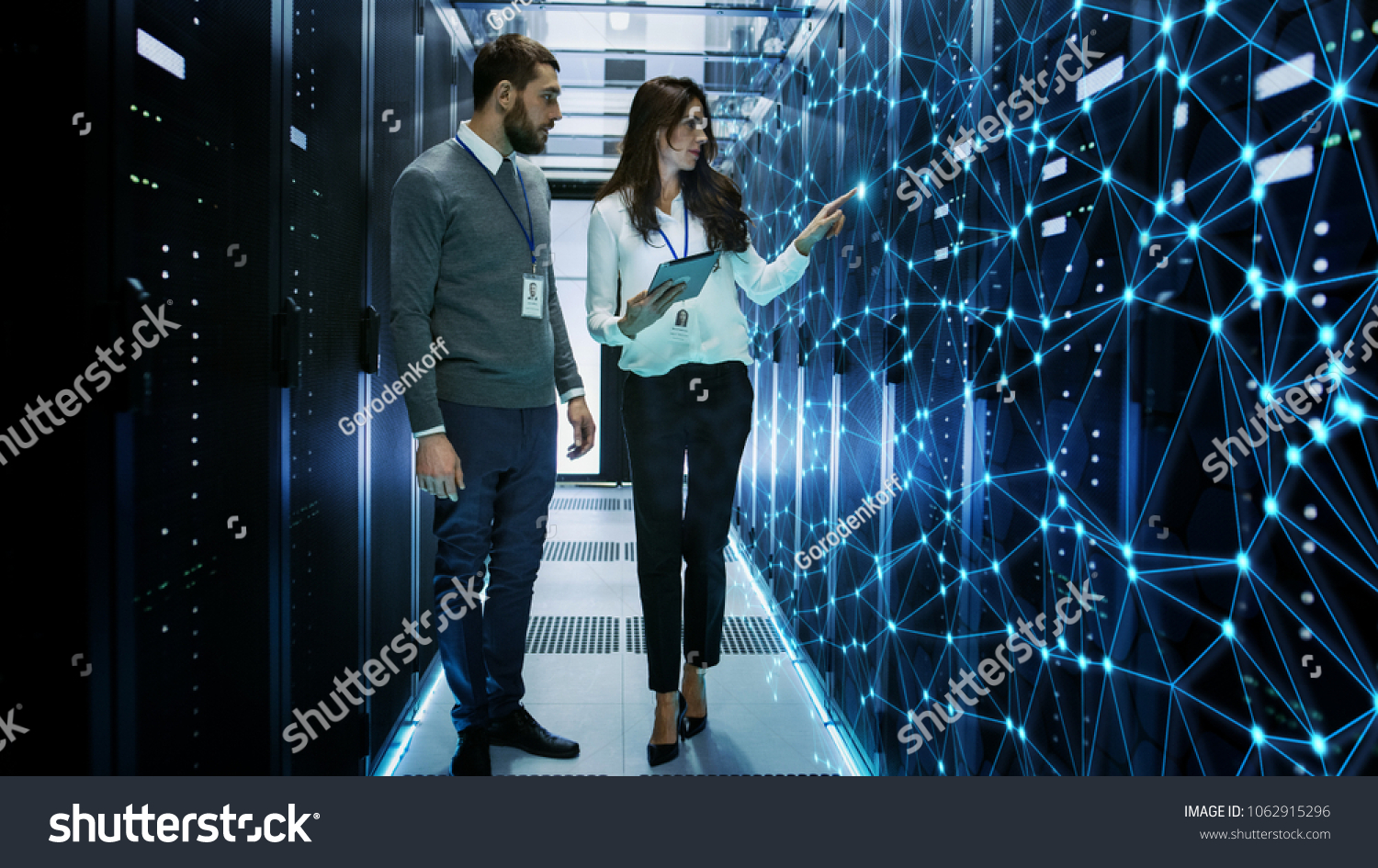 Female and Male IT Engineers Discussing Technical Details in a Working Data Center/ Server Room with Internet Connection Visualisation. #1062915296