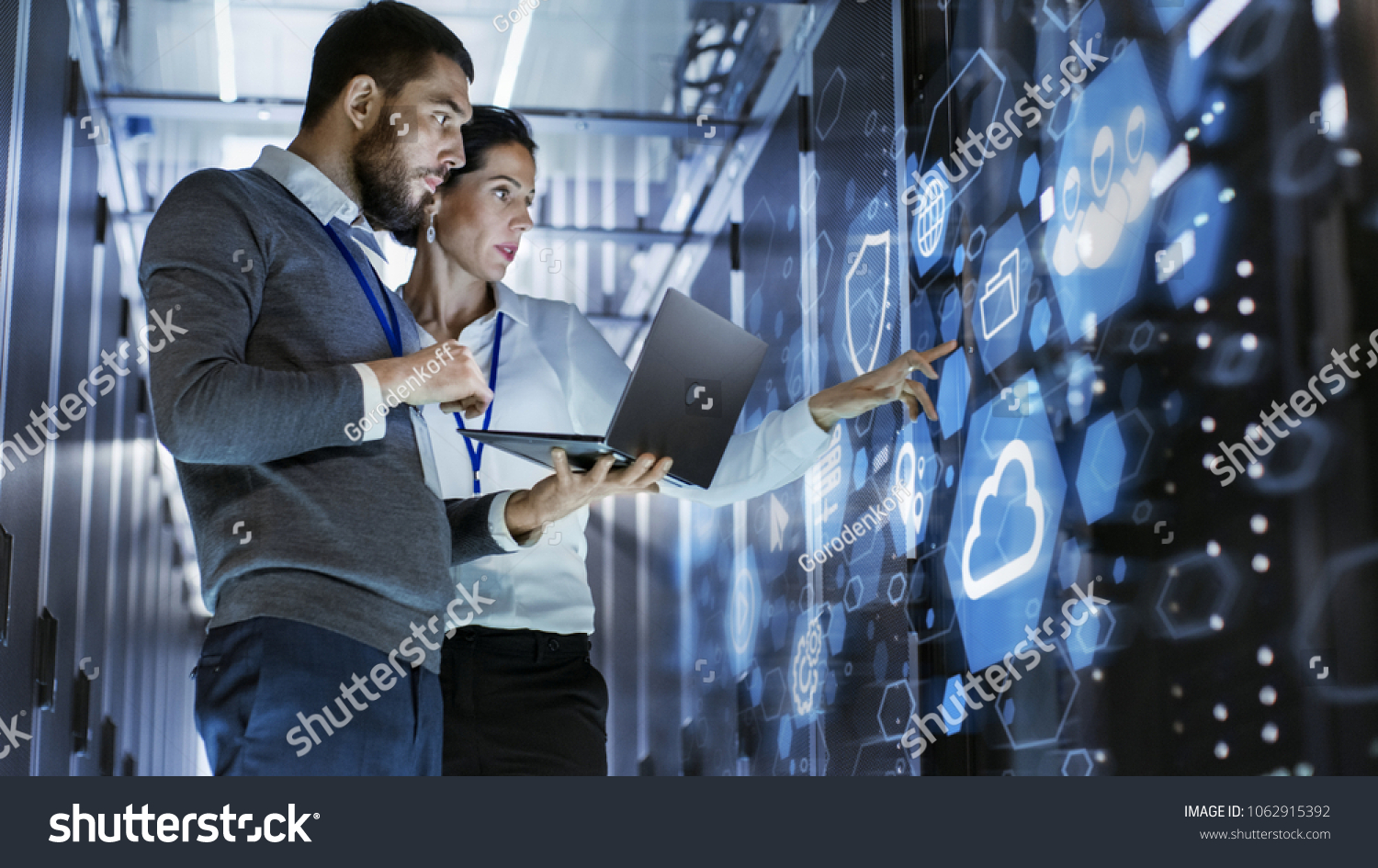 Male IT Specialist Holds Laptop and Discusses Work with Female Server Technician. They're Standing in Data Center, Rack Server Cabinet with Cloud Server Icon and Visualization. #1062915392