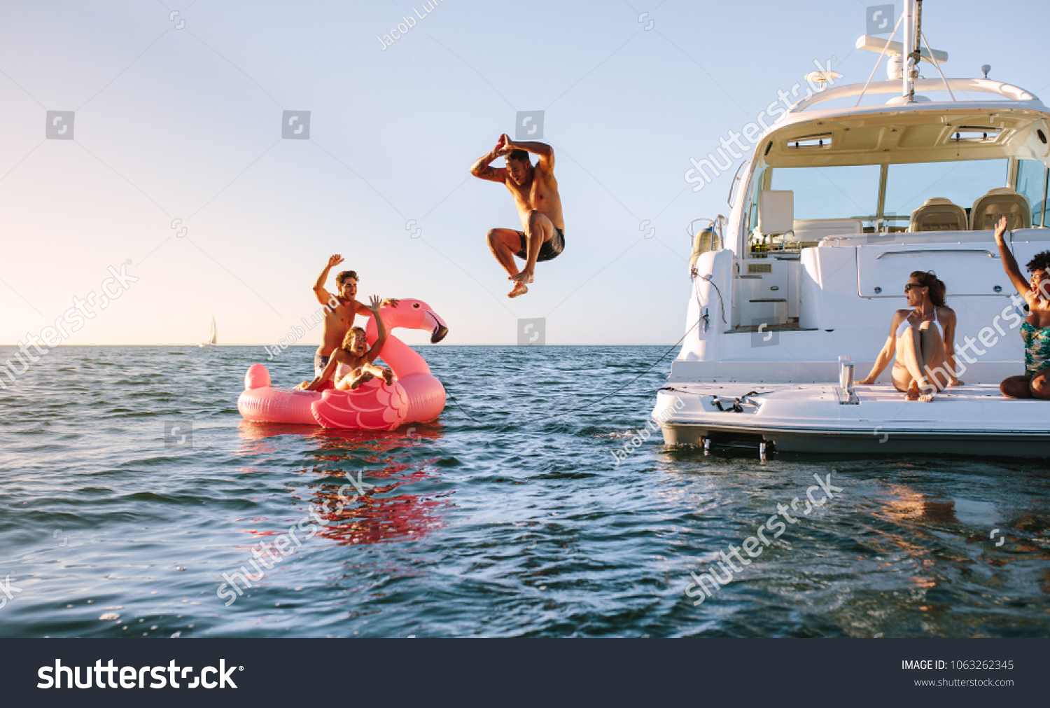 Man diving in the sea with friends sitting on yacht and inflatable toy. Group of friends enjoying a summer day on a inflatable toy and yacht. #1063262345