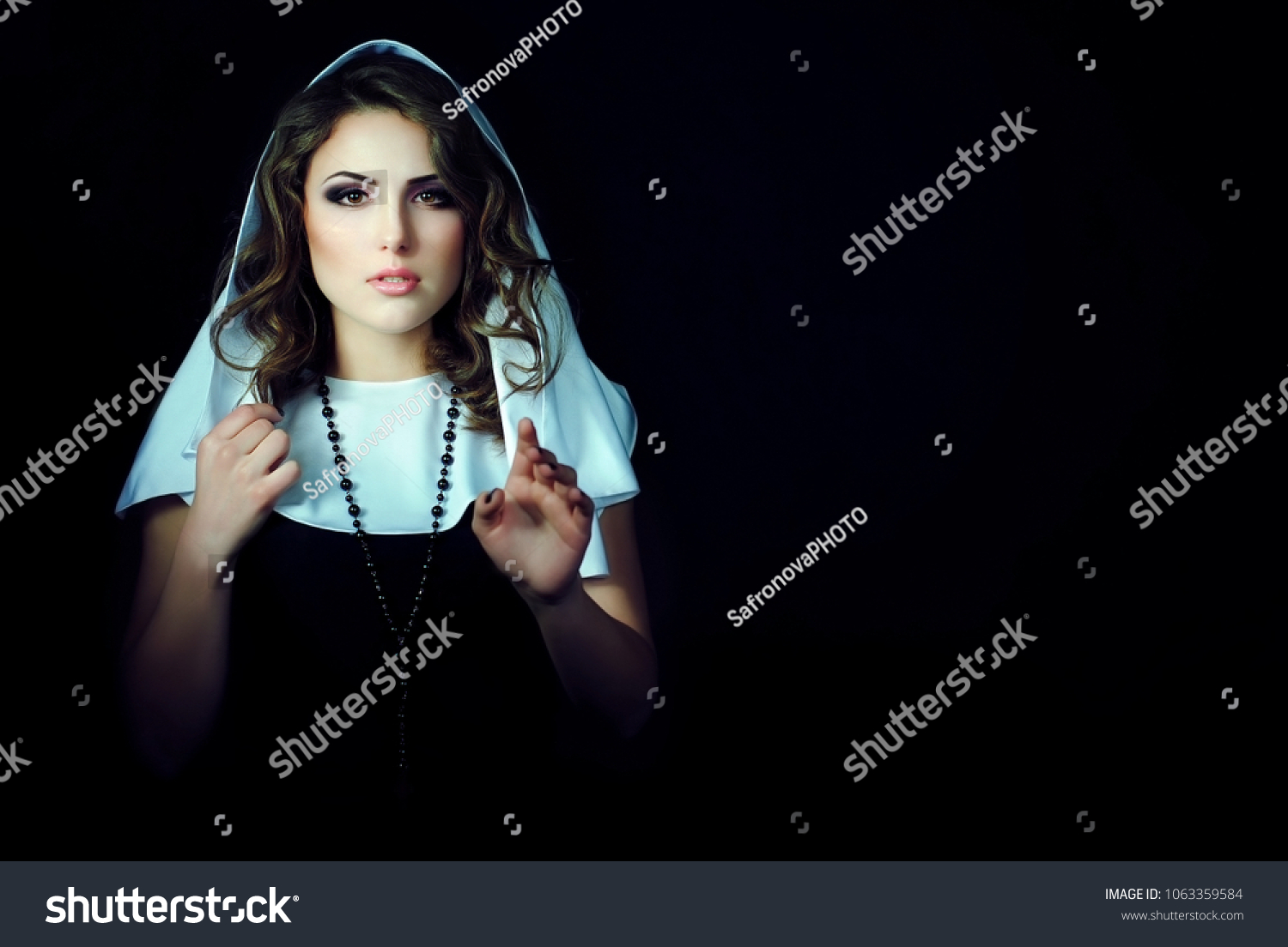 Bright makeup on the girl's face. A beautiful nun with a cross. Portrait of