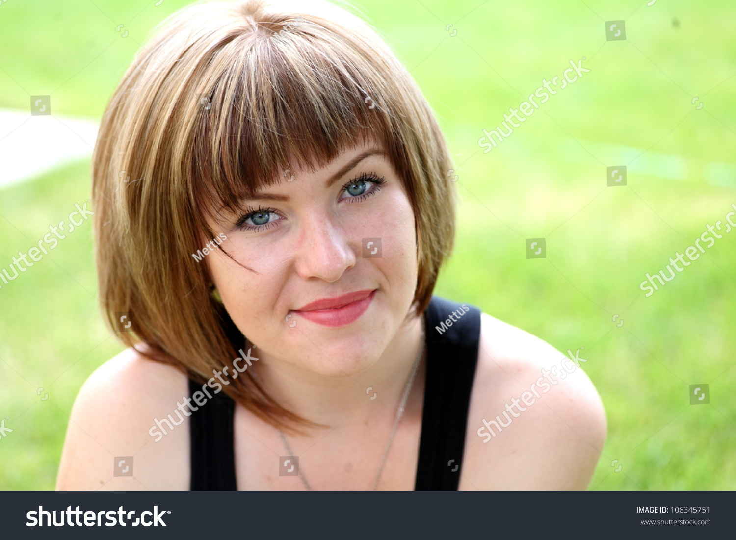 Closeup portrait of a happy blonde woman looking at camera against fresh green grass ,head and shoulders shot, young woman in town park