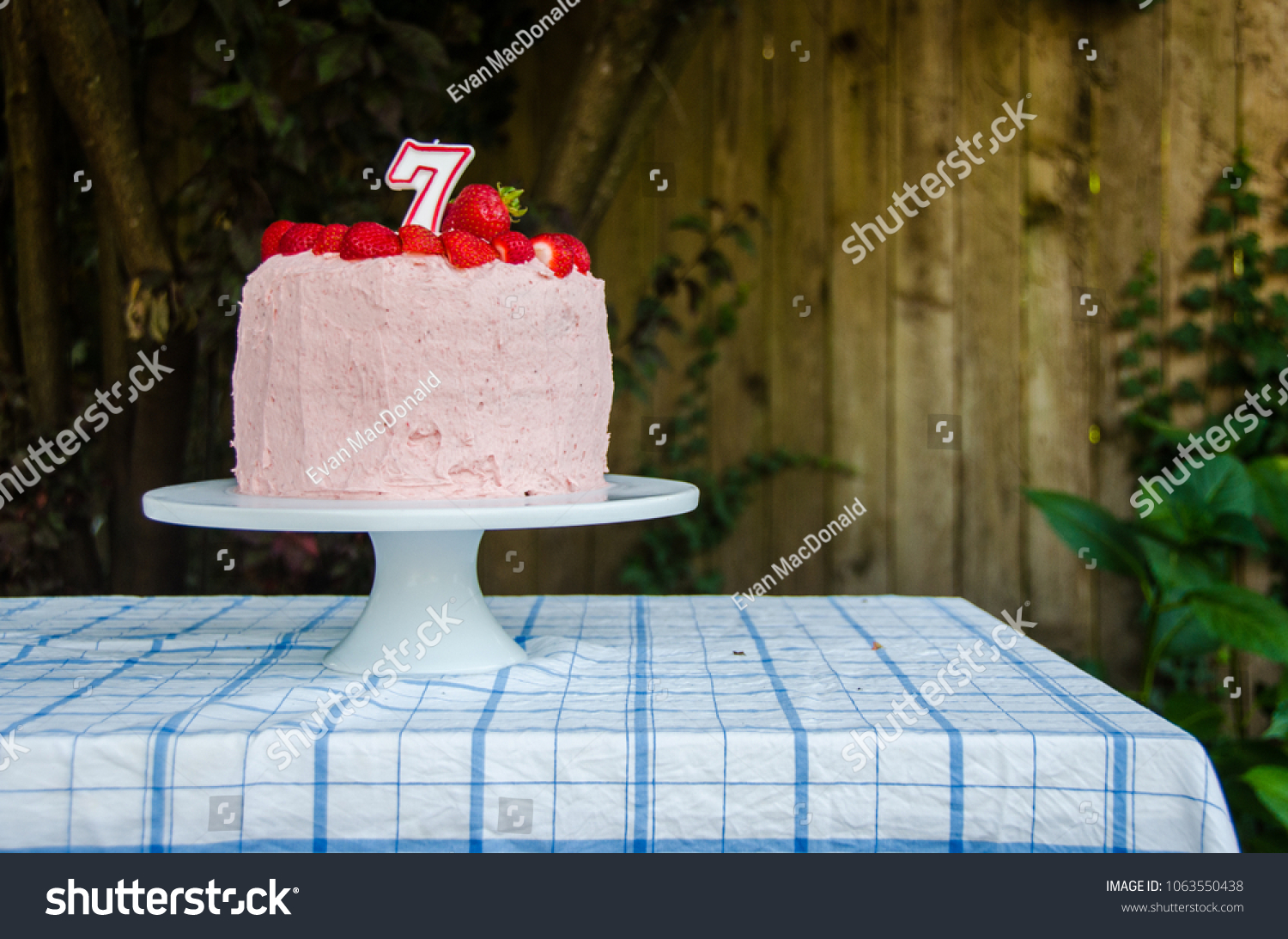 A Pink Frosted Birthday Cake On Table Outside With Strawberries And Candle Top
