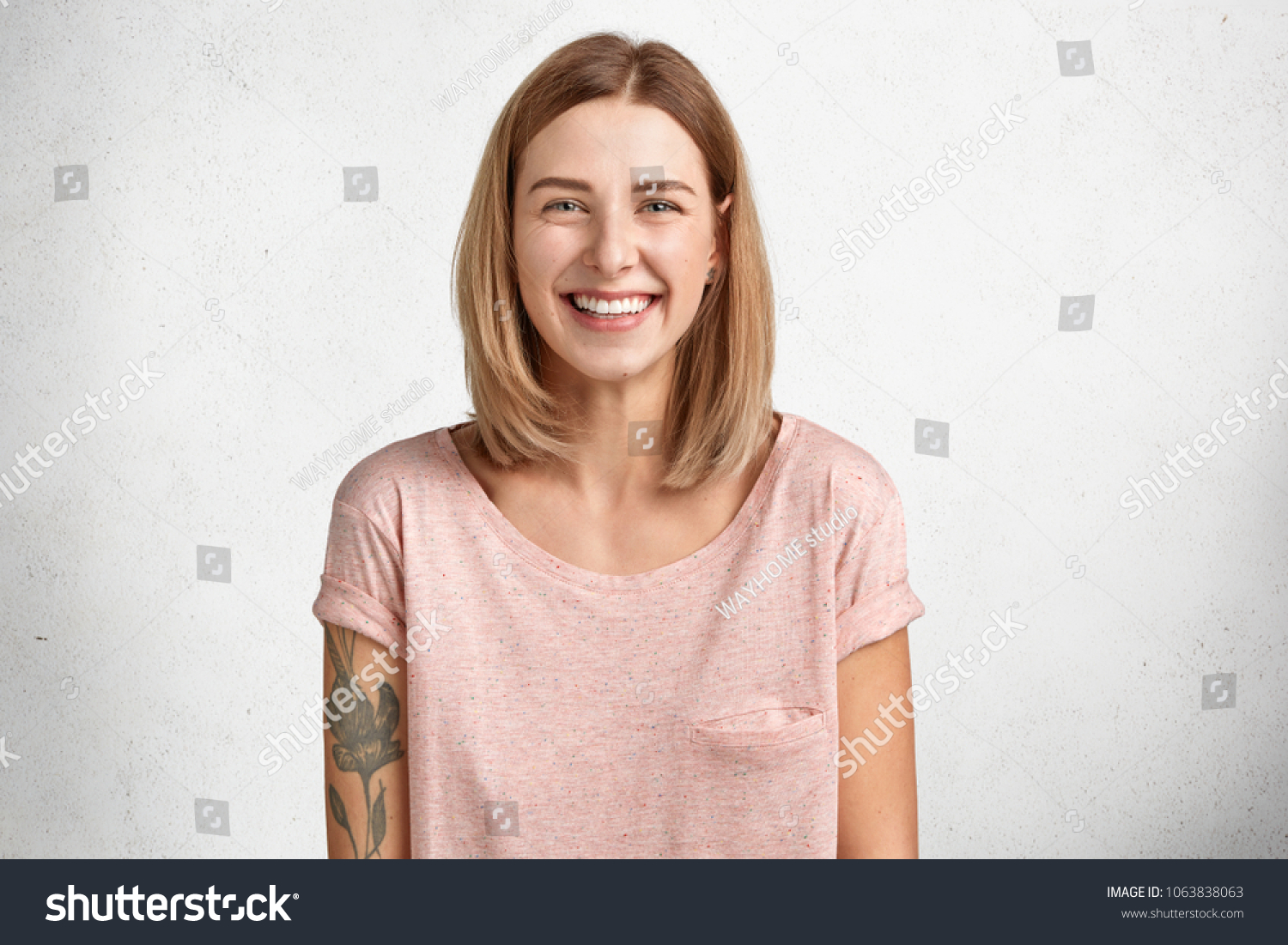 Happy delighted female with positive smile, has tattoo, smiles broadly, dressed in casual clothing, isolated over white concrete wall. Smiling adorable glad woman rejoices success and having weekends #1063838063