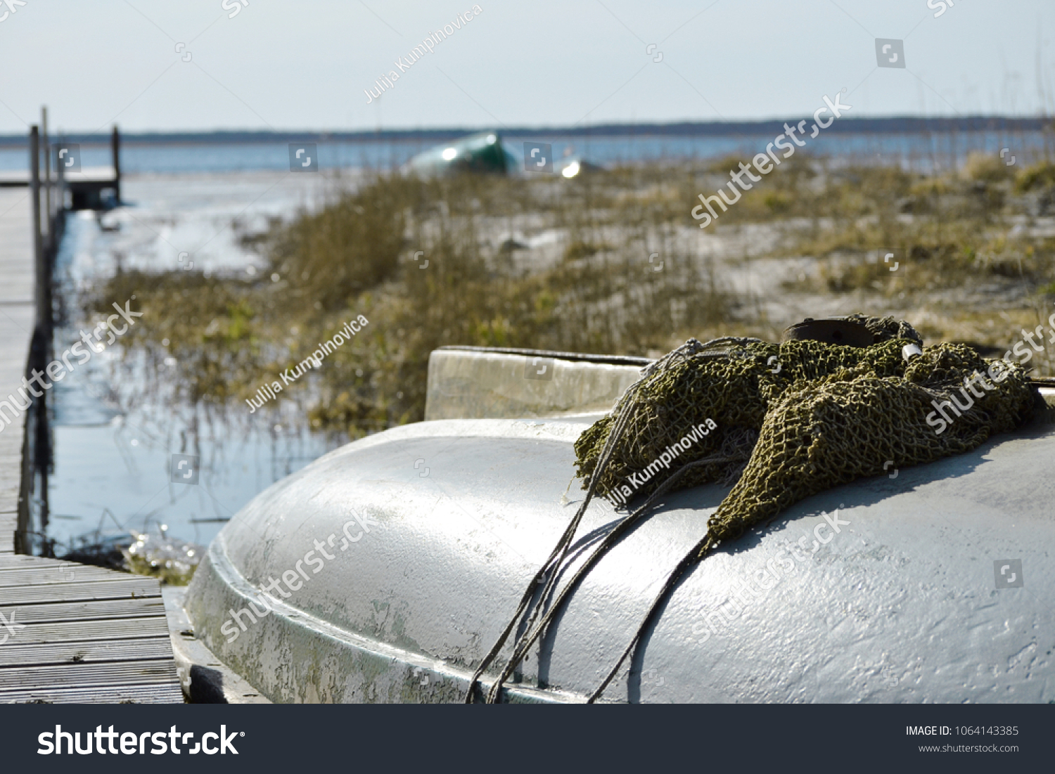 Fisherman boat with fishing net on the lake shore out of season at the early spring.