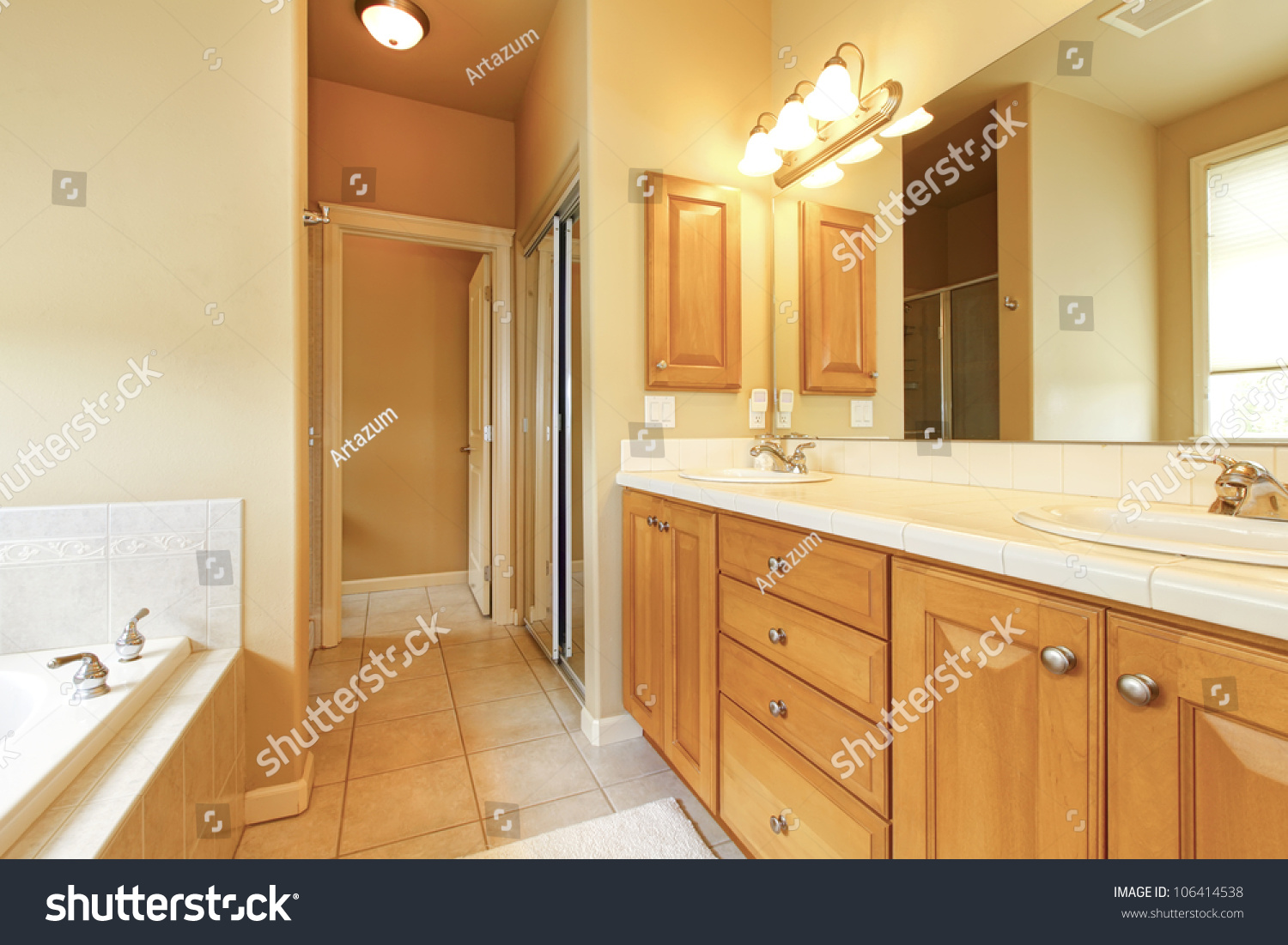 Bathroom Interior With Beige Tiles And Wood Cabinets
