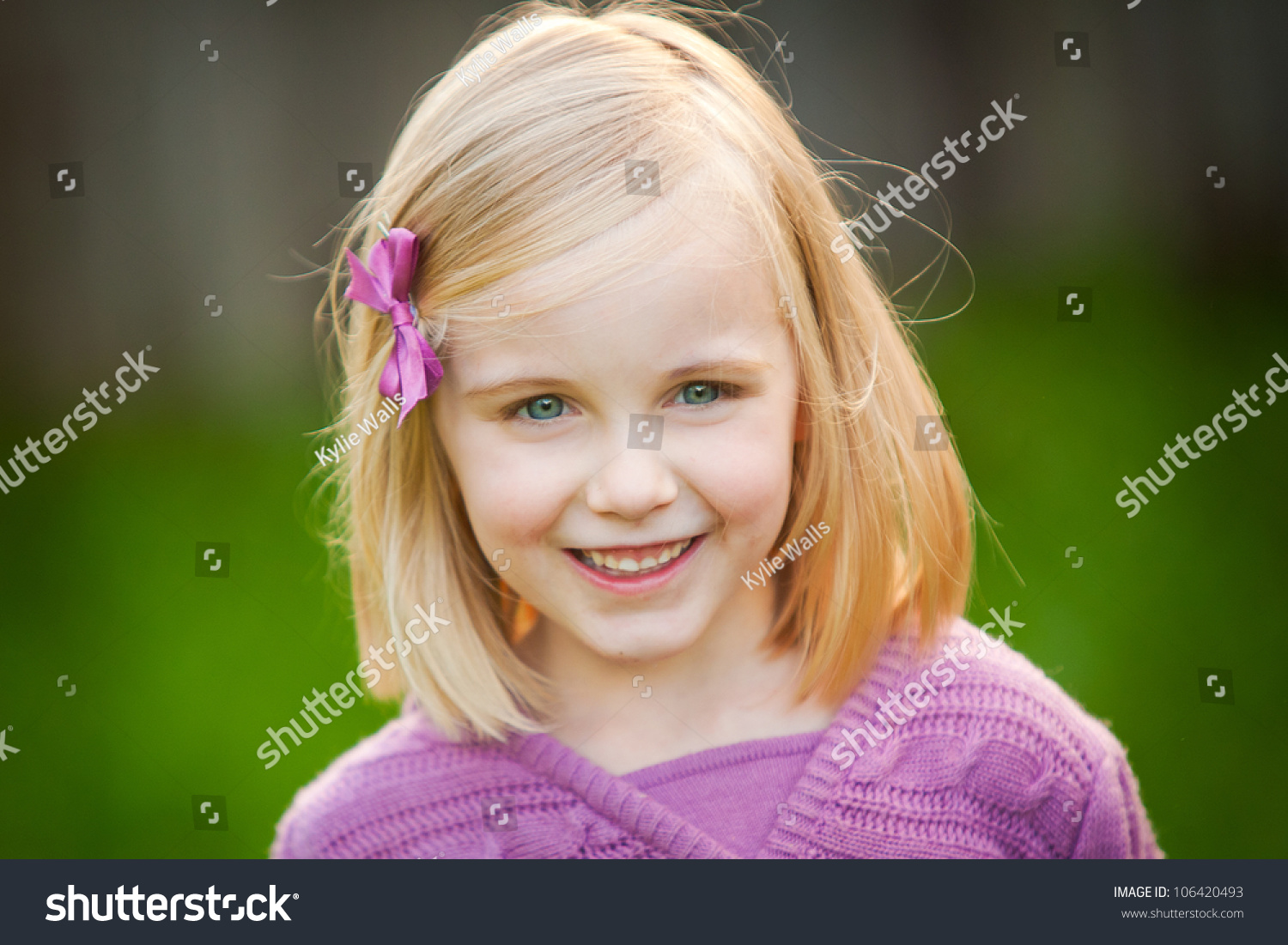 blonde little girl A cute blonde little girl is smiling at the camera. She is wearing a pink