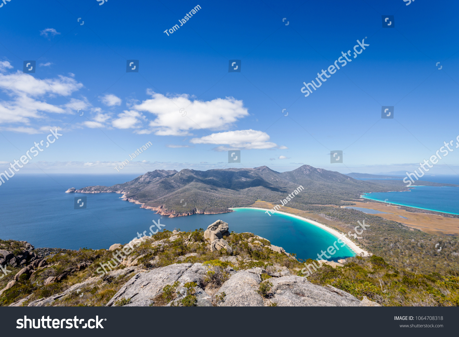 Relaxing amazing mountain viewpoint stunning view to Wineglass Bay sandy beach blue water and enjoyng warm sunny blue sky after hiking on top, Freycinet National Park, Mount Amos, Tasmania, Australia #1064708318