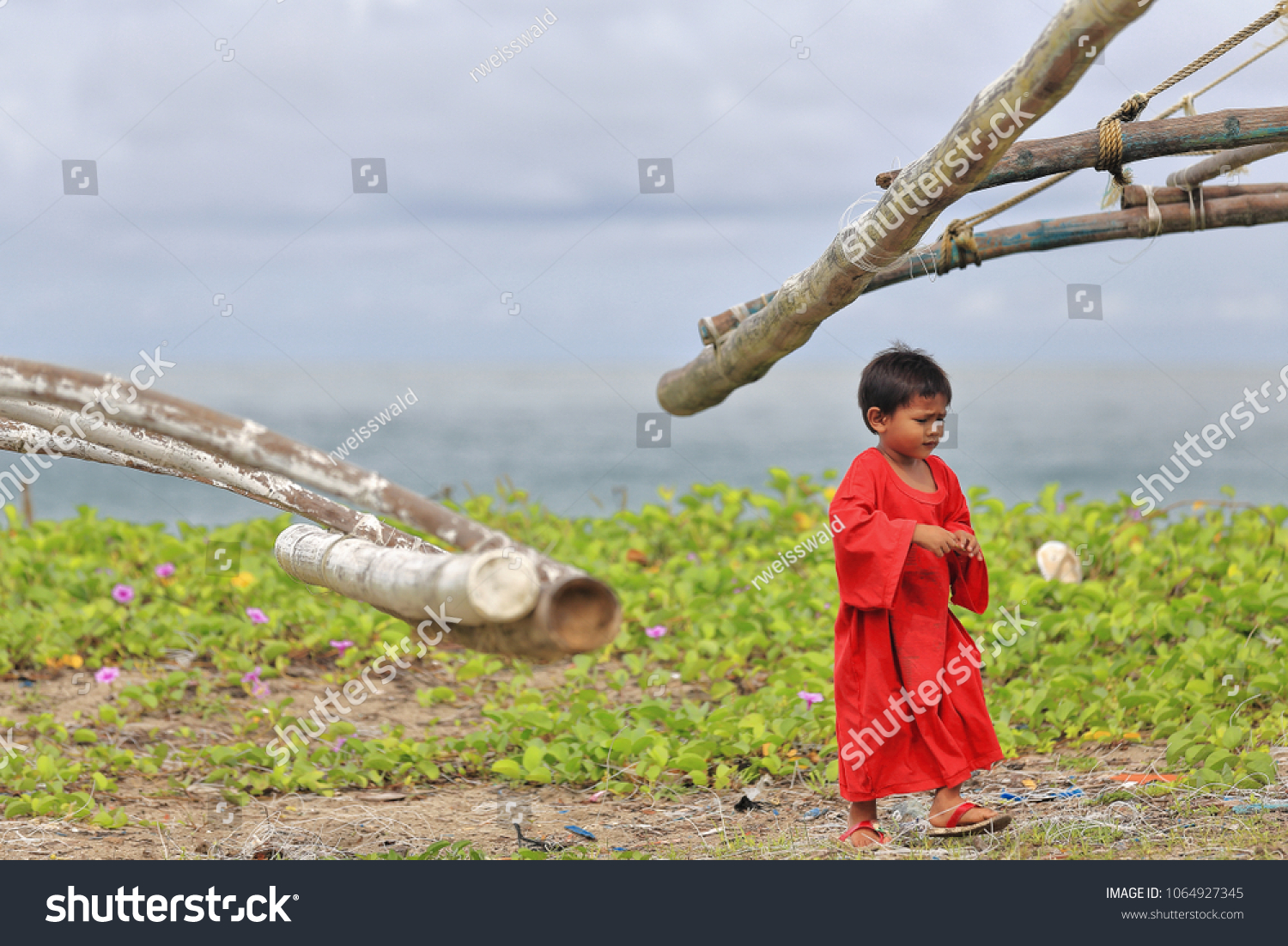 Sipalay, Philippines-October 13, 2016: Filipino young boy walks among and  gets