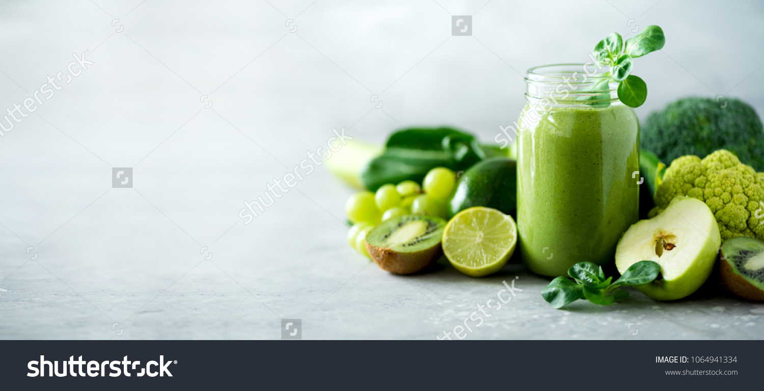 Glass jar mugs with green health smoothie, kale leaves, lime, apple, kiwi, grapes, banana, avocado, lettuce. Copy space. Raw, vegan, vegetarian, alkaline food concept. Banner. #1064941334