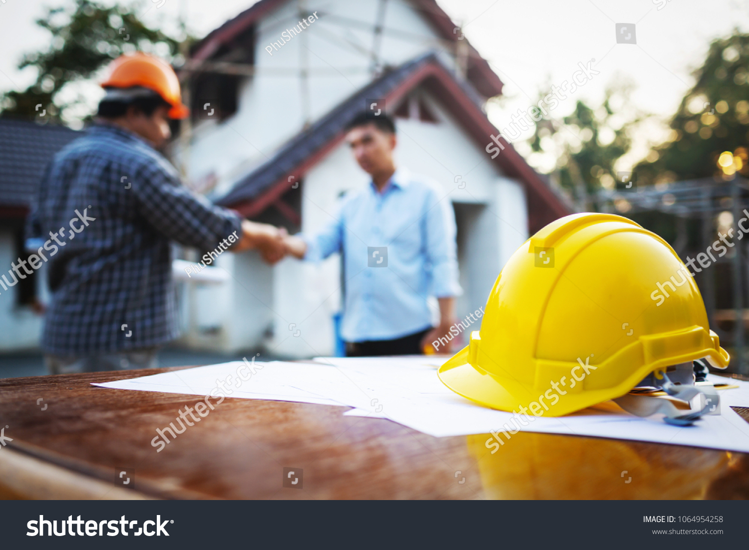 Shaking hands of partnership agreement between structural engineers and contractors to build houses. After agreeing the employment price and calculating the cost of construction and repair real estate #1064954258